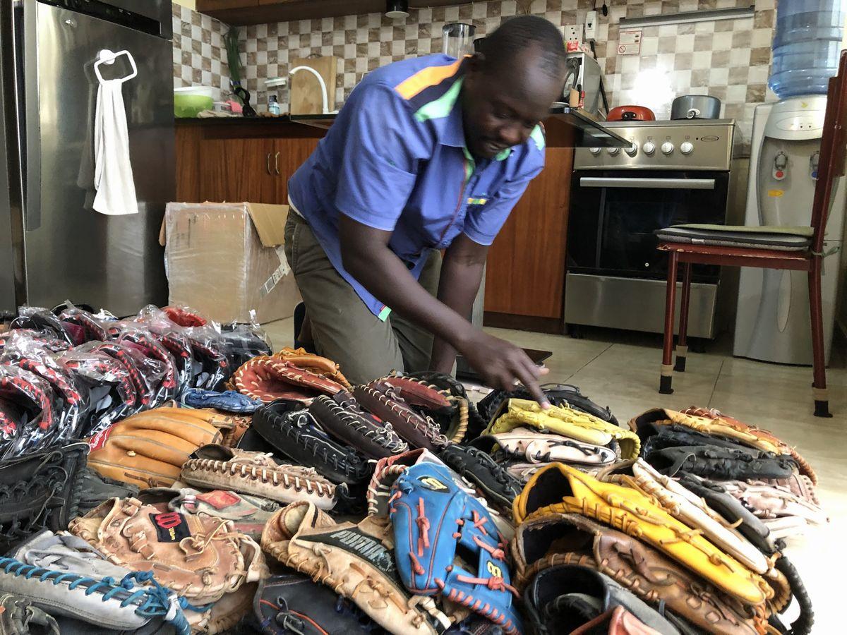 写真・図版 : 筆者の自宅に管理していた野球道具をすべて南スーダン野球・ソフトボール連盟に移管するため、まずは道具の数を確認。これらはすべて日本で集めてもってきたもの。ピーターが数を数えている。
