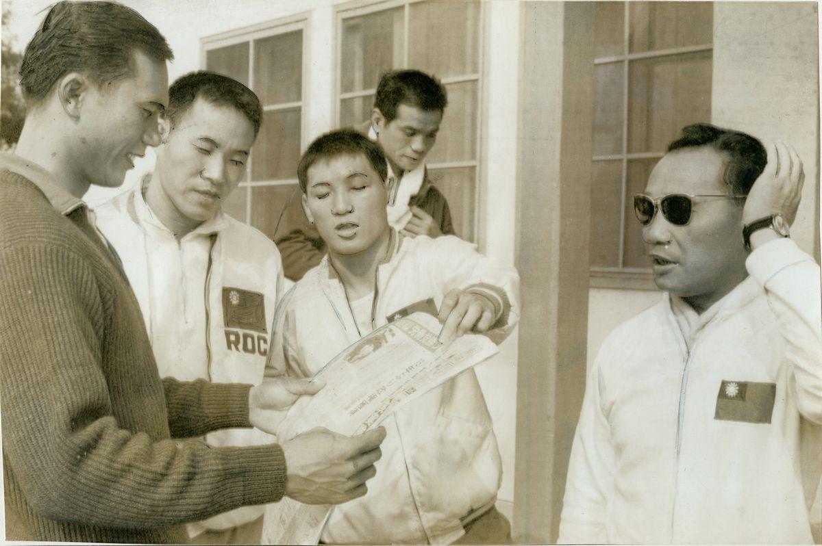 写真・図版 : 1964年10月の東京五輪中にあった中国の核実験を伝える新聞を見る台湾の選手たち=東京・代々木の五輪選手村