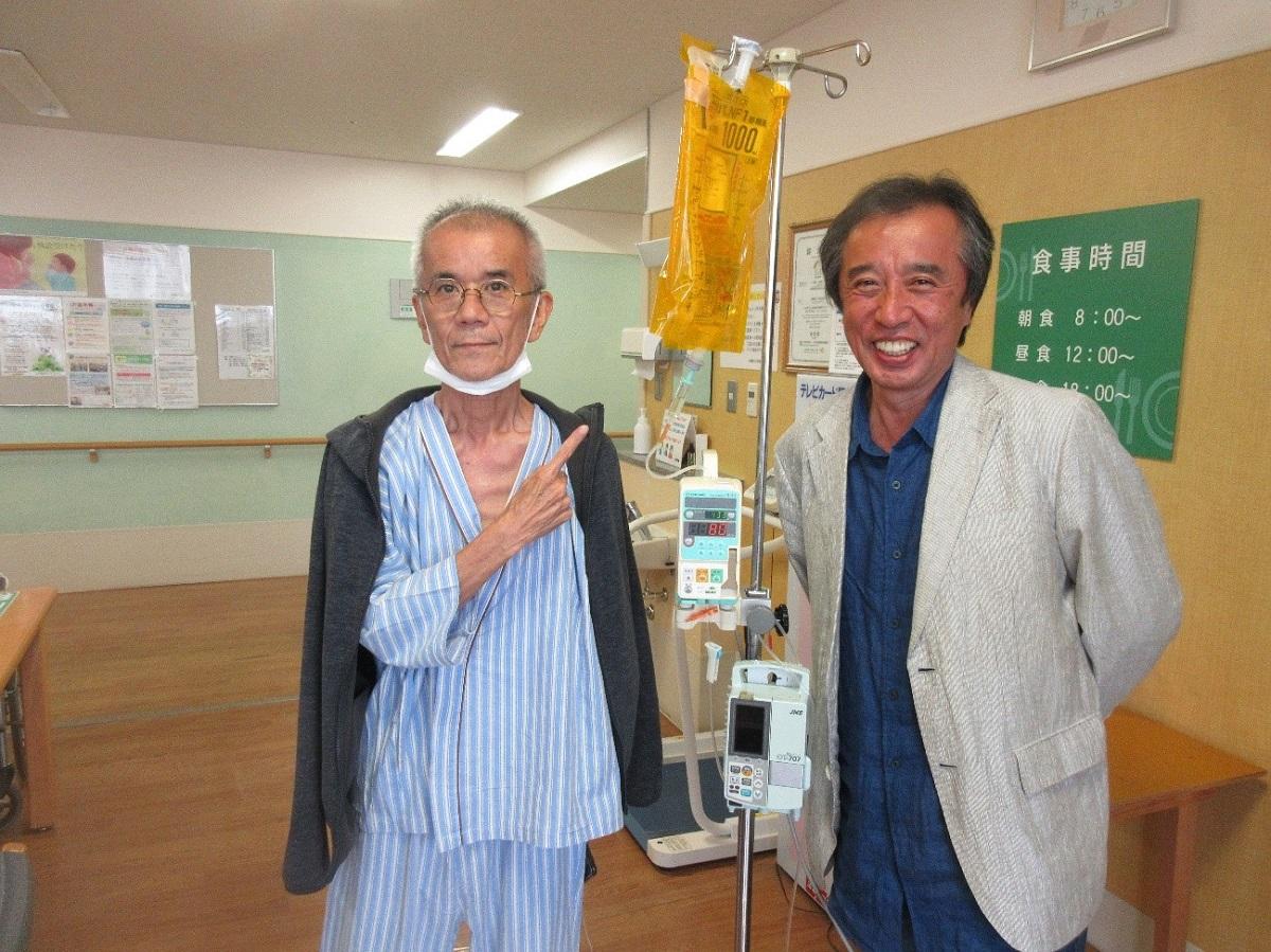 写真・図版 : 2019年4月、入院先の沖縄県立中部病院に盟友・大盛伸二さん(左)を見舞う=筆者提供