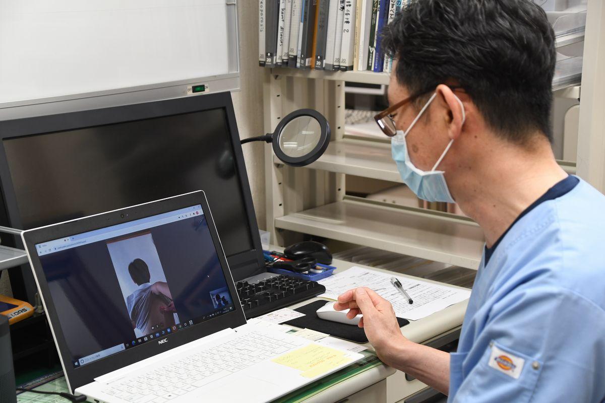 写真・図版 : オンライン診療の実証実験。医師がパソコン越しに患者役の男性を診察する=2020年8月18日、仙台市太白区