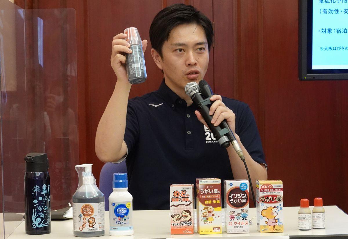 写真・図版 : うがい薬でのうがいを奨励する大阪府の吉村洋文知事=2020年8月4日、大阪府公館