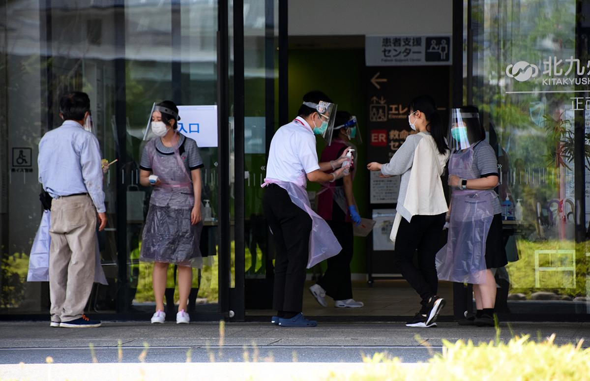 写真・図版 : 来院者に消毒などへの協力を求める病院職員ら=2020年5月29日、北九州市小倉北区、加治隼人撮影