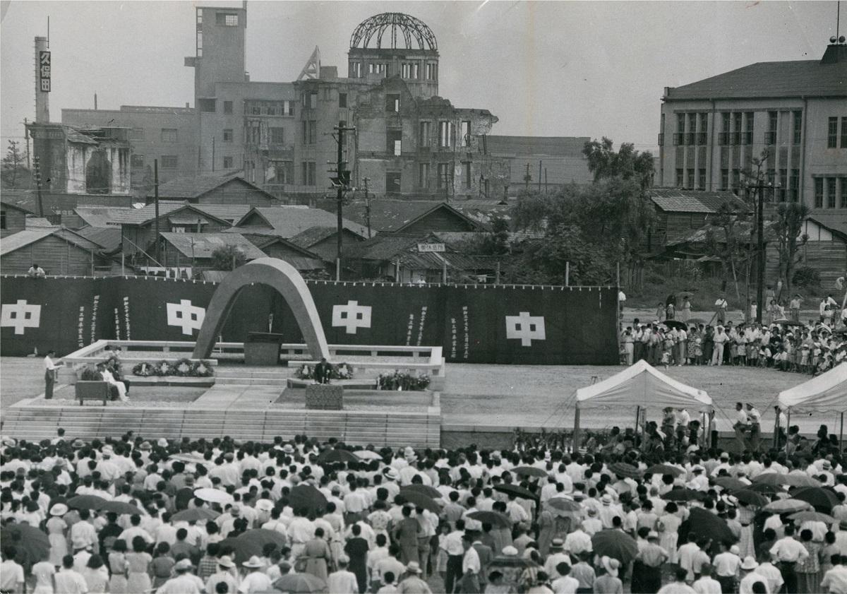 写真・図版 : 横断幕でバラックを遮って挙行された原爆慰霊式(1953年8月6日)