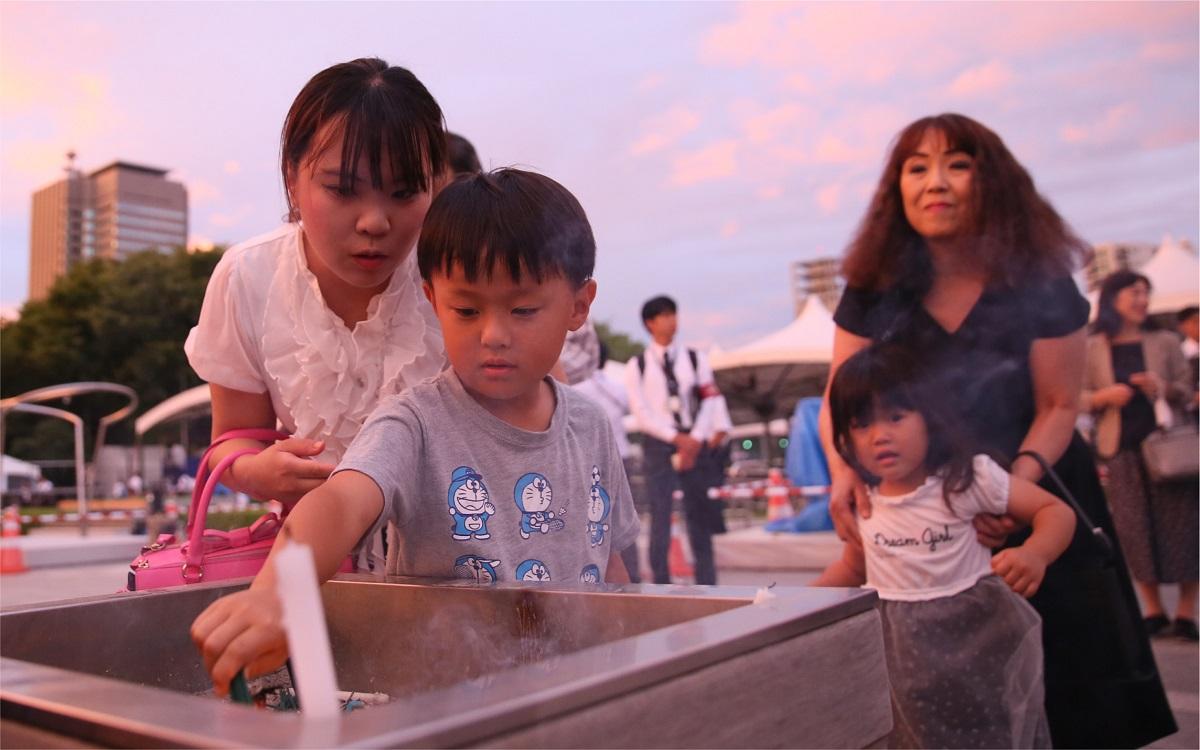 写真・図版 : 広島の原爆死没者慰霊碑の前で線香に火を付ける人たち=2019年8月6日、広島市中区