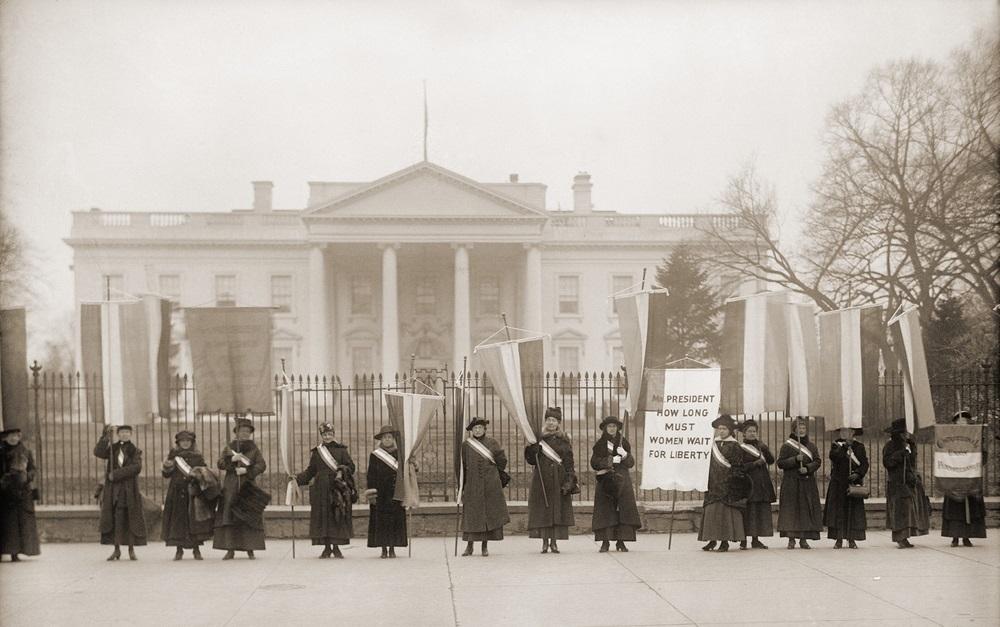 写真・図版 : ホワイトハウス前で女性参政権の実現を訴える女性たち=1918年、ワシントン