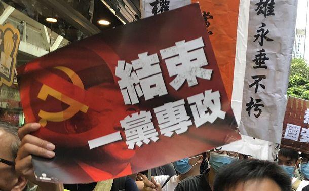 写真・図版 : 香港国家安全維持法の施行に反対するデモで掲げられた「(中国共産党の)一党独裁を終わらせよ」のプラカード=2020年7月1日、香港