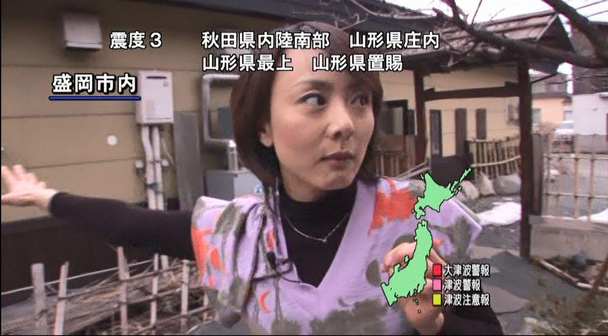 写真・図版 : 盛岡市内での取材中に東日本大震災が起き、余震が続く中でリポートするアナウンサー。テロップは余震の震度などを表している=2011年3月11日、岩手めんこいテレビ提供