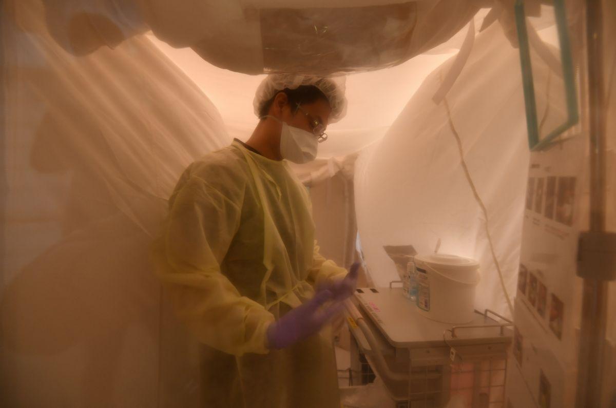 写真・図版 : 新型コロナウイルスに対応するため、医療従事者は過酷な現場を長時間担っている。写真は、新型コロナ専用病棟での診察や治療を終え、陰圧状態を保った空間で防護服を脱ぐ医師=4月24日