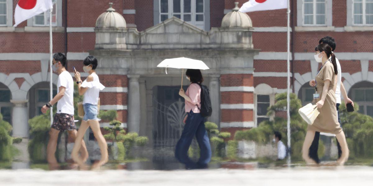 写真・図版 : 8月は全国的に猛暑が続く。東京駅付近では、炎天下をマスク姿の人々が行きかうなか、「逃げ水」が見られた=8月7日