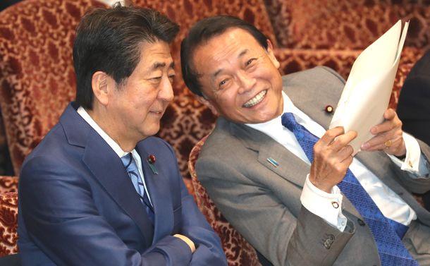 写真・図版 : 参院予算委の開会前、言葉を交わす安倍晋三首相(左)と麻生太郎財務相=2020年1月31日