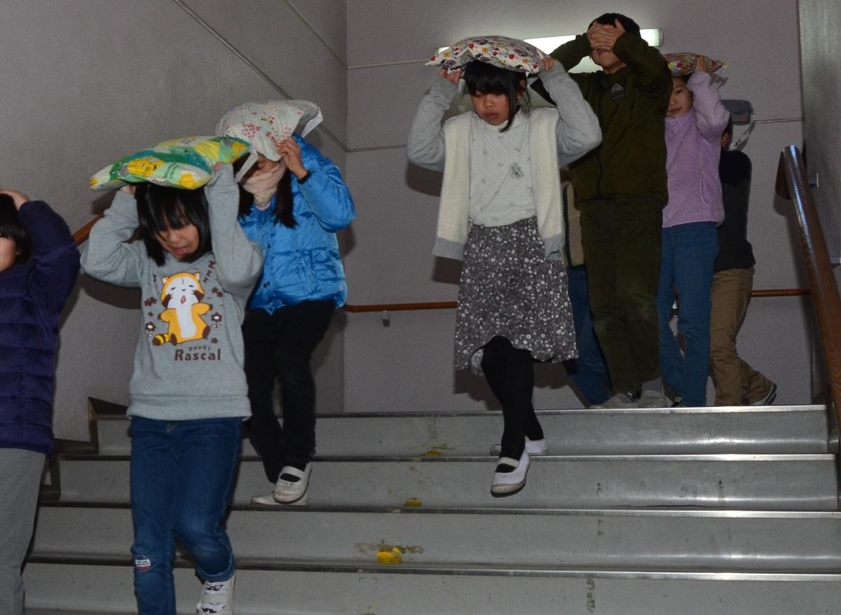 写真・図版 : 訓練で頭を座布団などで守りながら避難する児童たち=2019年1月17日、兵庫県篠山市の市立今田小学校