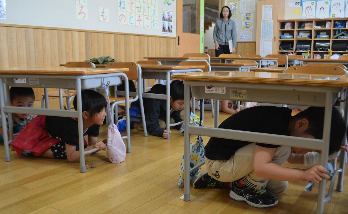 机の下で身を守る児童ら=2019年5月24日、秋田県北秋田市 201905