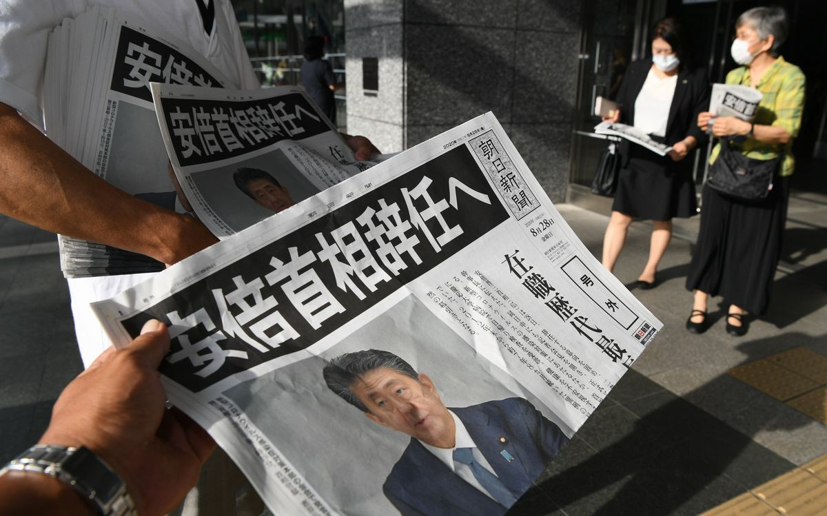 写真・図版 : 安倍首相辞職を伝える号外が配られ、受け取った人は足を止めて読んでいた=2020年8月28日午後4時40分、福岡市博多区