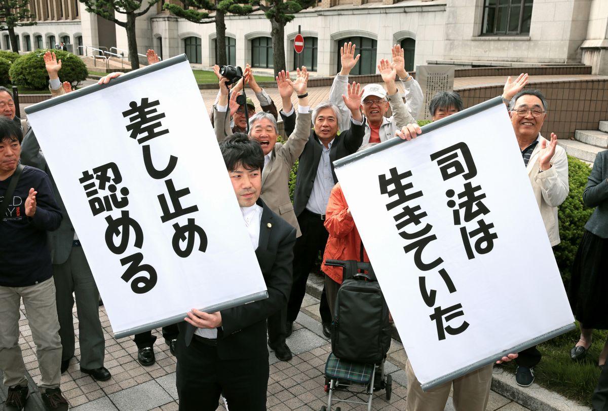 写真・図版 : 運転差し止めを命じる判決を支持者に伝える、原告団の弁護士ら=2014年5月21日、福井市の福井地裁前