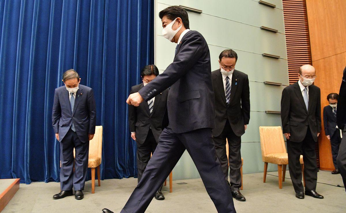 写真・図版 : 辞任表明の会見に臨む安倍晋三首相(手前)。左端は菅義偉官房長官=2020年8月28日午後5時、首相官邸
