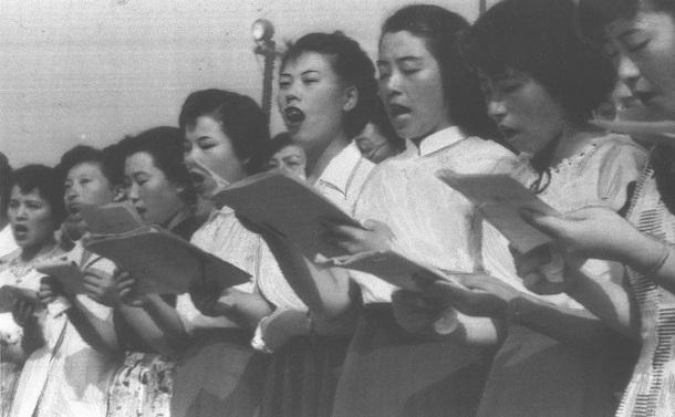 写真・図版 : 原爆10周年の原爆死没者慰霊式・平和記念式で「原爆を許すまじ」を大合唱する女性の合唱団=1955年8月6日、広島市の広島平和記念公園