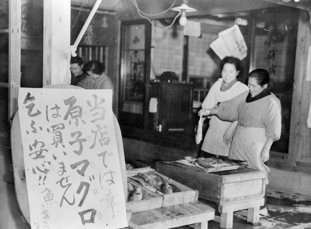 写真・図版 : 核実験の放射能で汚染されたマグロは仕入れていないと張り紙を出した鮮魚店=1954年3月1日、静岡県焼津市