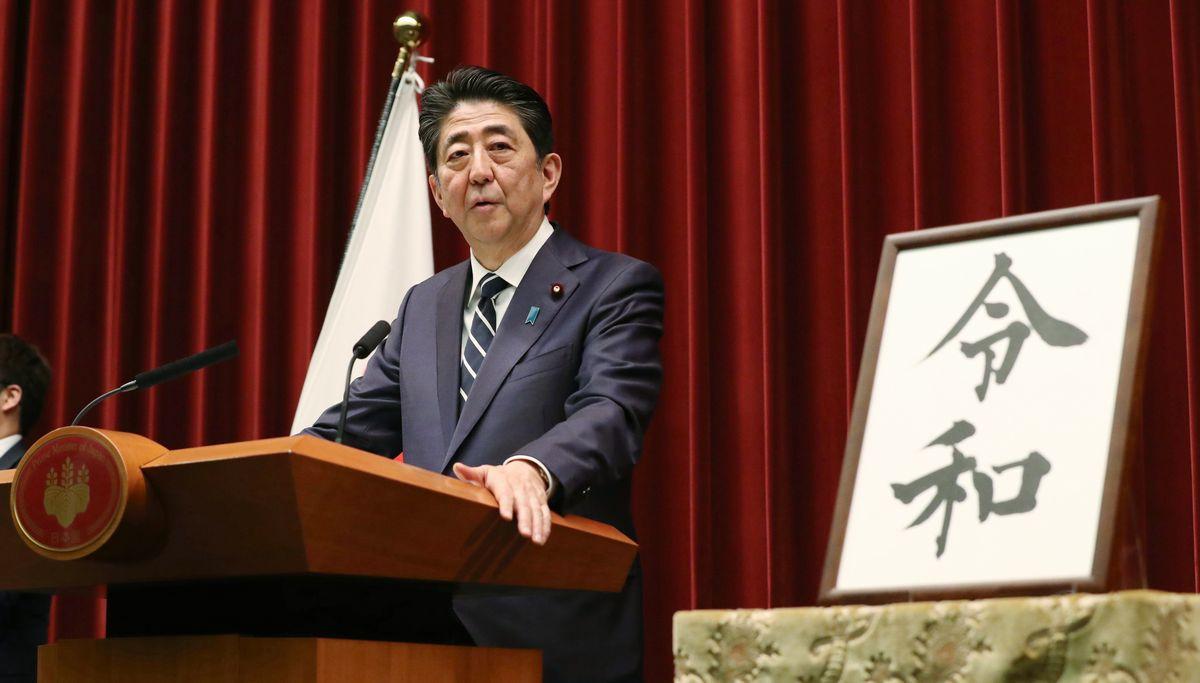 写真・図版 : 新元号「令和」の書を傍らに、記者会見する安倍晋三首相=2019年4月1日、首相官邸