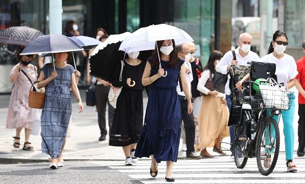 写真・図版 : 猛暑の中でもほとんどの人がマスクをつけている=2020年8月7日、東京都中央区、藤原伸雄撮影