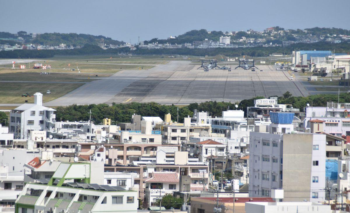 写真・図版 : 街の真ん中に位置する米軍普天間飛行場。遠くにオスプレイが見える=2020年2月20日、沖縄県宜野湾市