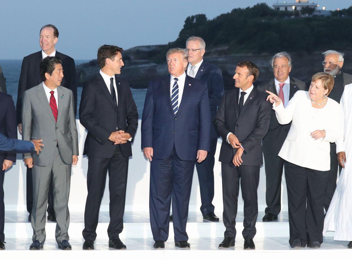 写真・図版 : 写真撮影の前に言葉を交わすG7サミット拡大会合の各国首脳ら。前列左から安倍晋三首相、トルドー加首相、トランプ米大統領、マクロン仏大統領、メルケル独首相=2019年8月25日、フランス・ビアリッツ