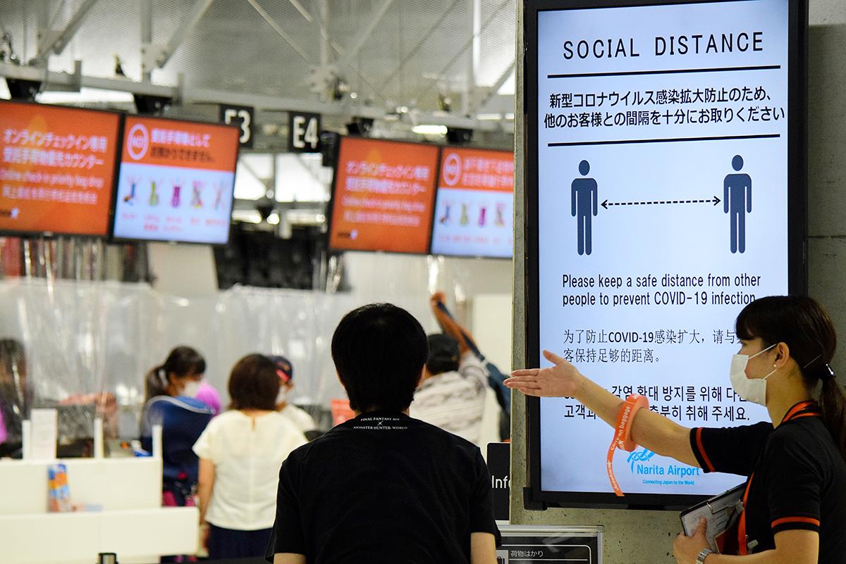 写真・図版 : 感染対策を求める表示が掲げられた空港ロビー=2020年7月23日、成田空港、福田祥史撮影