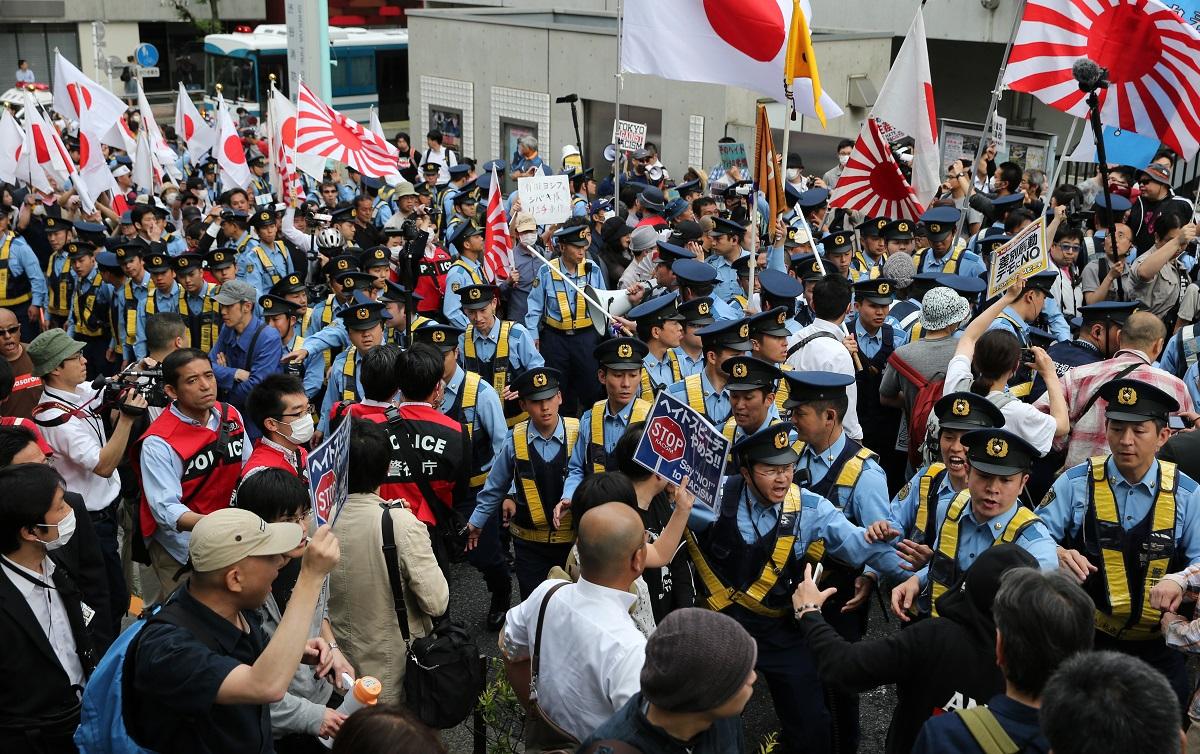 写真・図版 : 旭日旗をかかげたヘイトデモと、それに抗議する人々(手前)=2016年6月5日、東京・渋谷