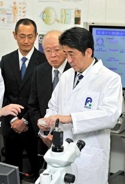 写真・図版 : 神戸市内で医療研究施設を視察する安倍首相(右)。野依良治・理化学研究所理事長(中央)やiPS細胞を研究する山中伸弥・京都大教授(左)が説明した=2013年1月11日、代表撮影