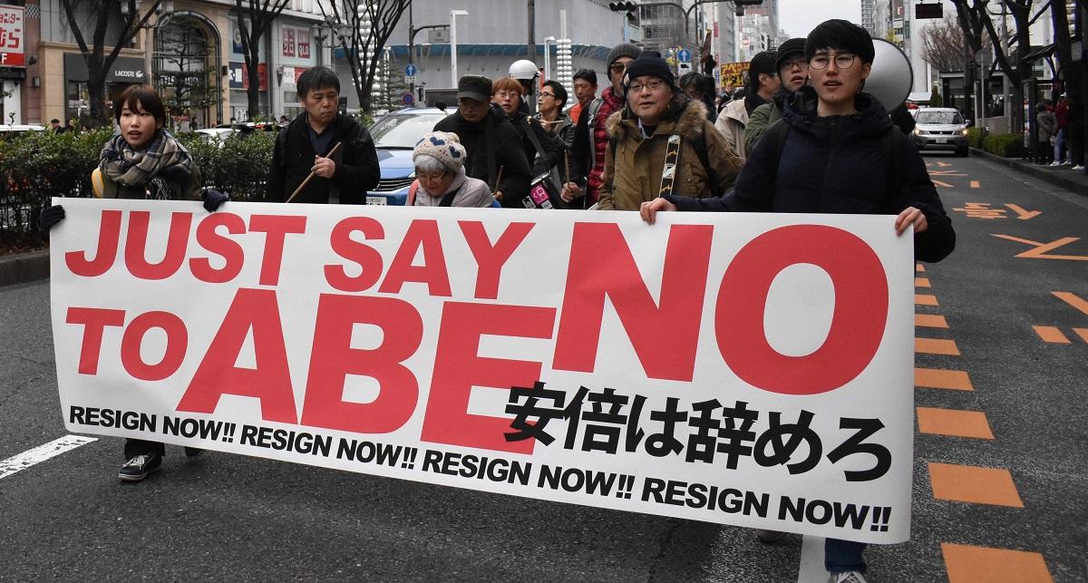 安倍首相の退陣を求める横断幕を掲げ、繁華街を歩くデモ参加者=2020年1月12日午後1時59分、名古屋市中区、202001