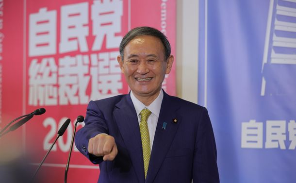 写真・図版 : カメラマンの求めに応じて拳を突き出す自民党の菅義偉新総裁=2020年9月14日、東京・永田町