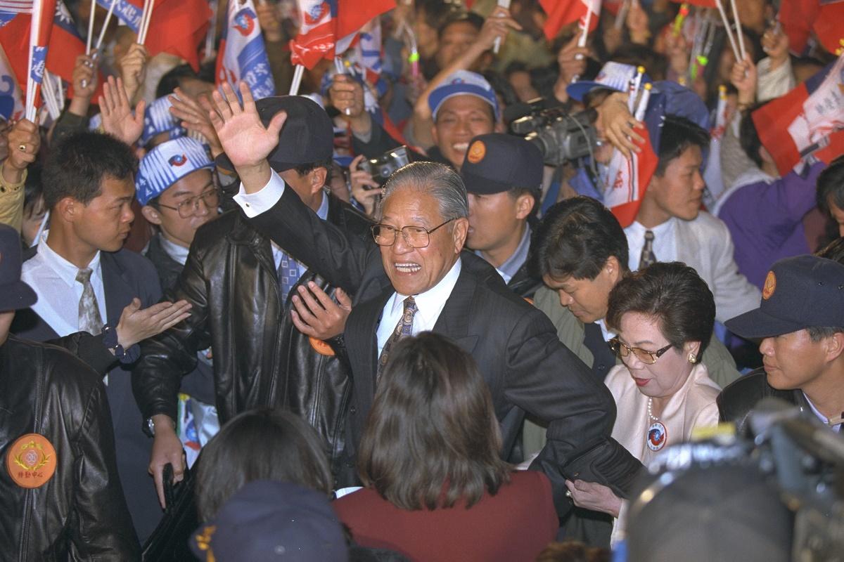 写真・図版 : 総統選で当選を決め、笑顔で支持者にこたえる李登輝氏(中央)=1996年3月23日、台北市内