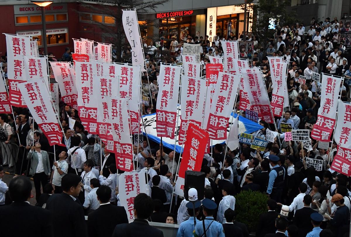 写真・図版 : 2018年の自民党総裁選最終日、安倍晋三首相の街頭演説中に首相に批判的な声があがると、支持者らが反対派の視界を遮るようにのぼり旗を掲げた=2018年9月19日、東京・秋葉原
