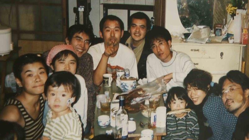 写真・図版 : 映画「沈没家族」の一場面。加納土氏(左から2人目)が、母の穂子氏(左端)のほか、たくさんの「保育人」の若者たちに囲まれている©おじゃりやれフィルム