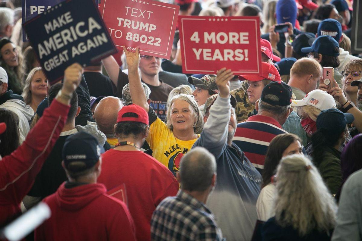 写真・図版 : 飛行機の格納庫で行われたトランプ大統領の選挙集会で、「あと4年!」や「米国を再び偉大に」などと書かれたプラカードを掲げる支持者たち=ミシガン州フリーランド、ランハム裕子撮影、2020年9月10日