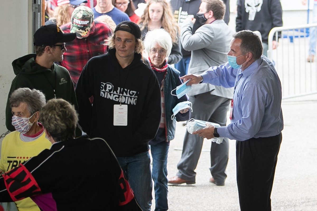 写真・図版 : トランプ大統領の選挙集会の入り口で、配られるマスクの受け取りを拒否する支持者=ミシガン州フリーランド、ランハム裕子撮影、2020年9月10日