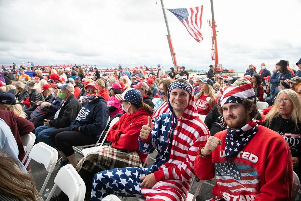 写真・図版 : トランプ大統領の選挙集会で、星条旗がデザインされた服をまといトランプ大統領の登場を待つ支持者たち=ミシガン州フリーランド、ランハム裕子撮影、2020年9月10日