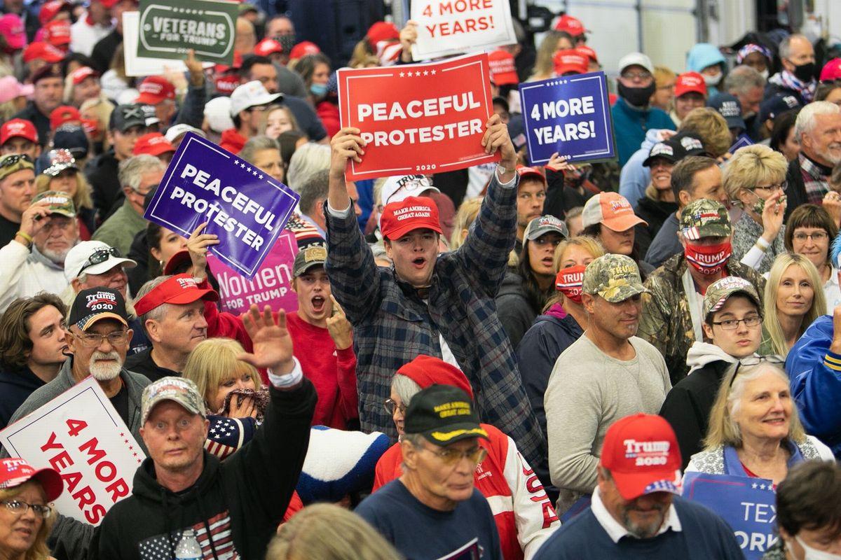写真・図版 : 2飛行機の格納庫で行われたトランプ大統領の選挙集会で、「あと4年!」や「米国を再び偉大に」などと書かれたプラカードを掲げる支持者たち=ミシガン州フリーランド、ランハム裕子撮影、020年9月10日