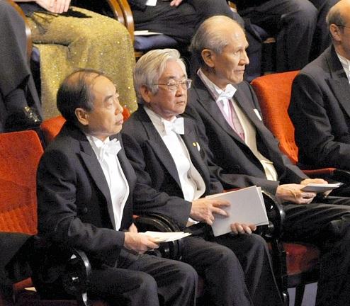 写真・図版 : ノーベル賞授賞式で着席した(左端から)小林誠さん、益川敏英さん、下村脩さんら=2008年12月10日、ストックホルム市内のコンサートホール