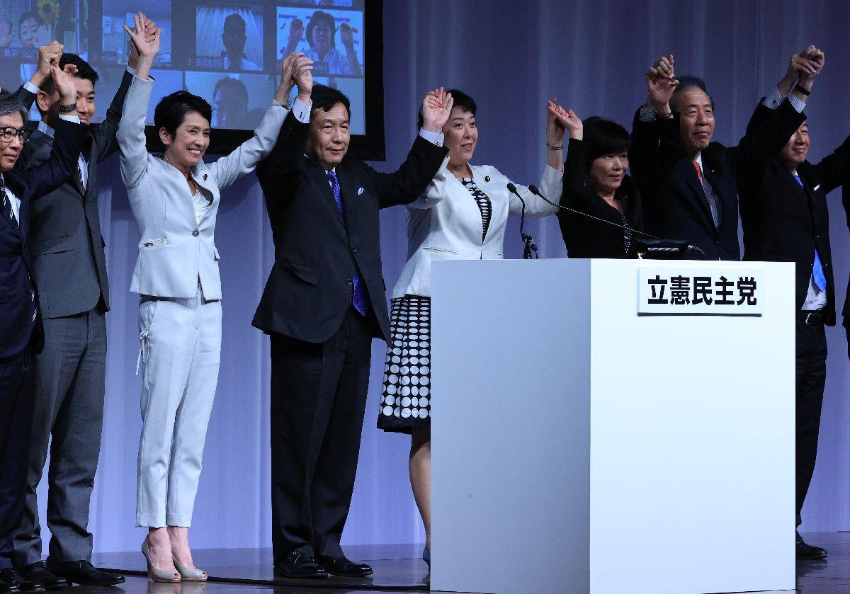 写真・図版 : 結党大会で執行部のメンバーと壇上に上がり、手をつなぐ立憲民主党の枝野幸男代表(中央左)=2020年9月15日午後2時26分、東京都港区