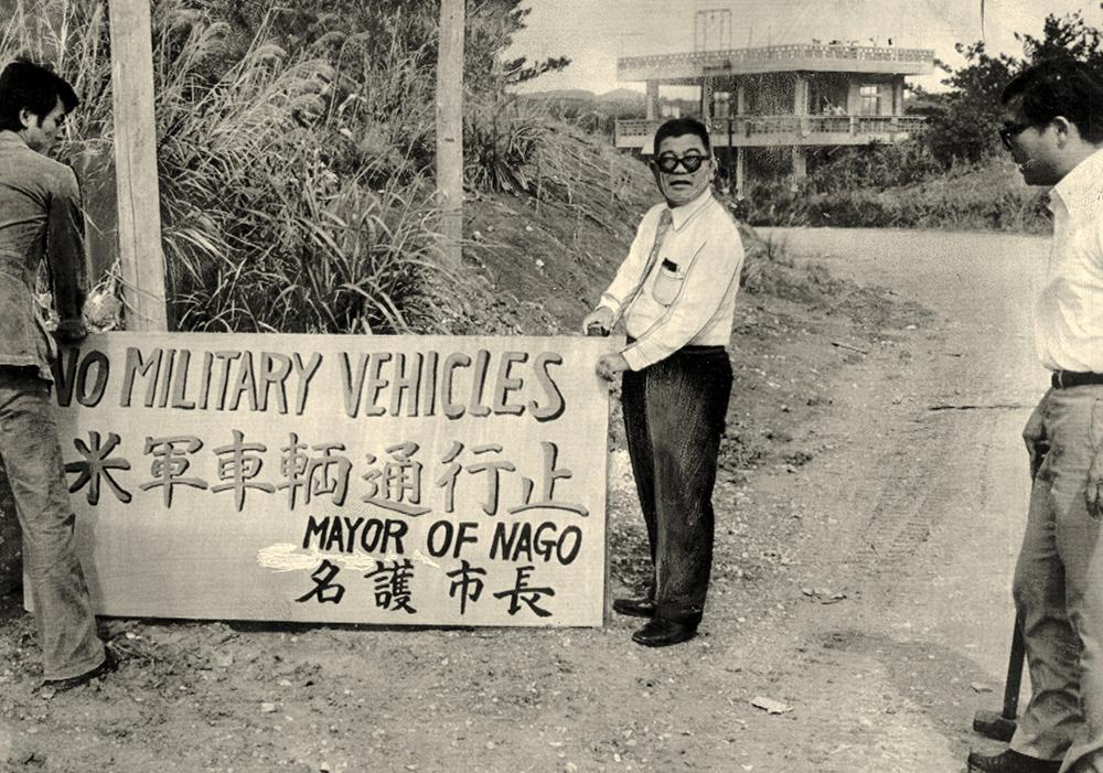 写真・図版 : 名護市久志で「米軍車輌通行止 名護市長」の立て札を立てる渡具知裕徳・名護市長= 1978年2月10日