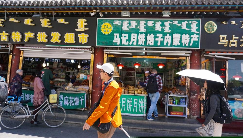 写真・図版 : 縦書きのモンゴル文字と漢字が併記されたフフホト市内の商店の看板  RosnaniMusa / Shutterstock.com
