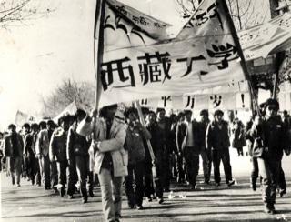 写真・図版 : 1988年12月30日、ラサのチベット大学生の抗議活動(旗は寮のカーテンで作成)。参加していたSonam Dorjee(当時、チベット語チベット文学部生)氏より提供。