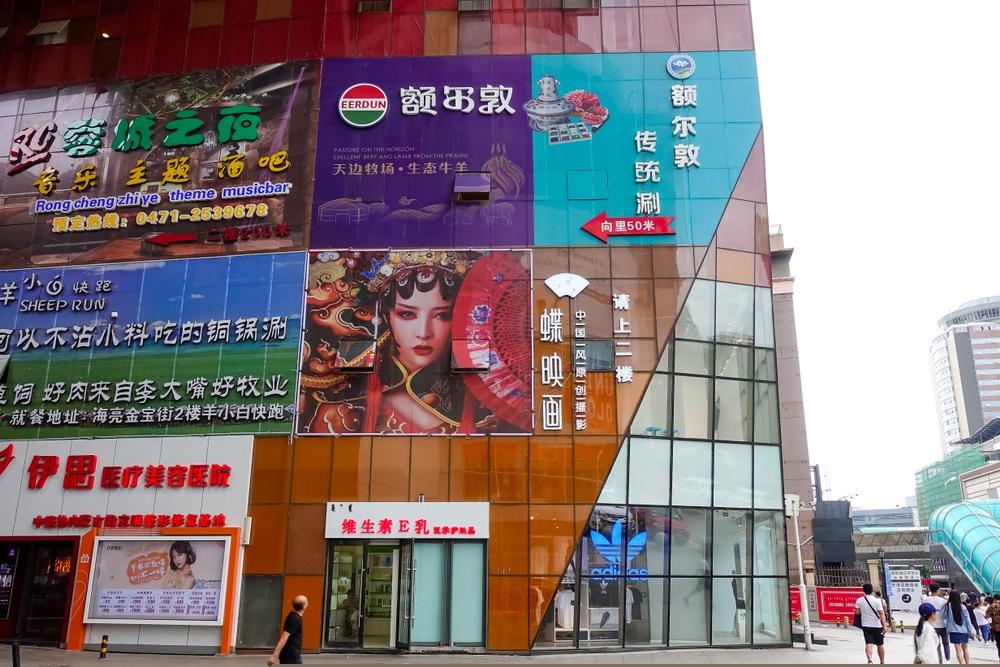 写真・図版 : フフホト市内の商業施設。内モンゴル自治区では交通標識などはモンゴル文字の併記が義務づけられているが、漢字だけの看板も多い。 Carlos Huang / Shutterstock.com