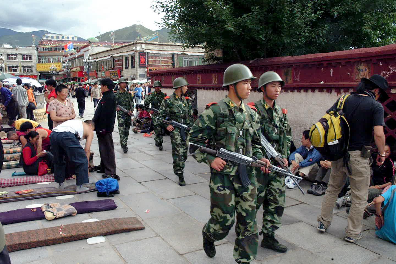 写真・図版 : ラサ旧市街のジョカン寺前を巡回する武装警察部隊=2008年8月21日