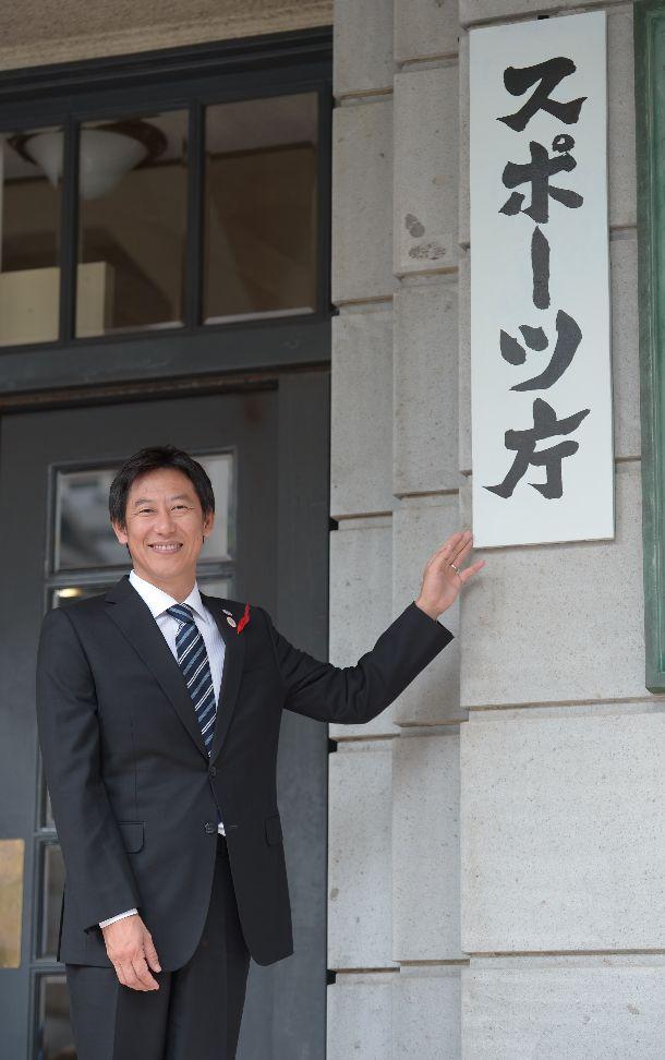 写真・図版 : スポーツ庁が発足。看板前に立つ鈴木大地長官=2015年10月1日、東京都千代田区