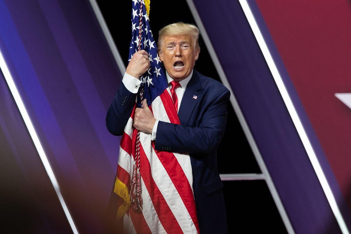 写真・図版 : 保守政治活動会議で演説後、米国旗に抱きつくトランプ大統領=2月、メリーランド州。朝日新聞社