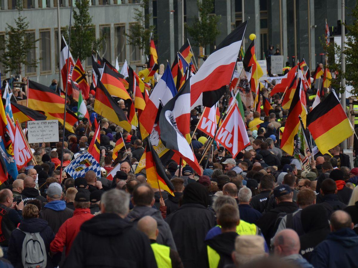 写真・図版 : 今のドイツ国旗とともに、かつてのドイツ帝国旗(中央)を振って練り歩く右翼団体の集会参加者=2019年10月、ベルリン。朝日新聞社