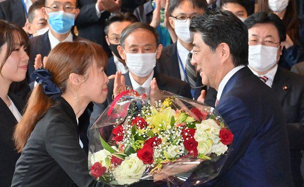 首相官邸のスタッフから花束を受け取る安倍晋三首相。中央は菅義偉官房長官(いずれも当時)=2020年9月16日