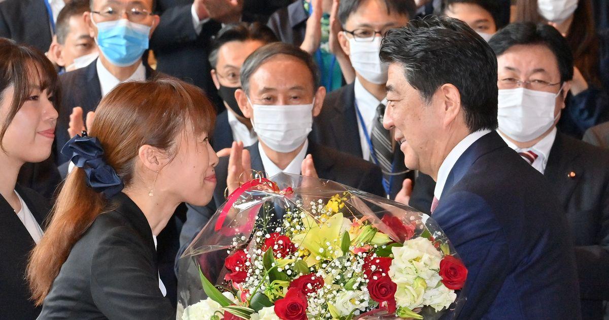 写真・図版 : 首相官邸のスタッフから花束を受け取る安倍晋三首相。中央は菅義偉官房長官(いずれも当時)=2020年9月16日