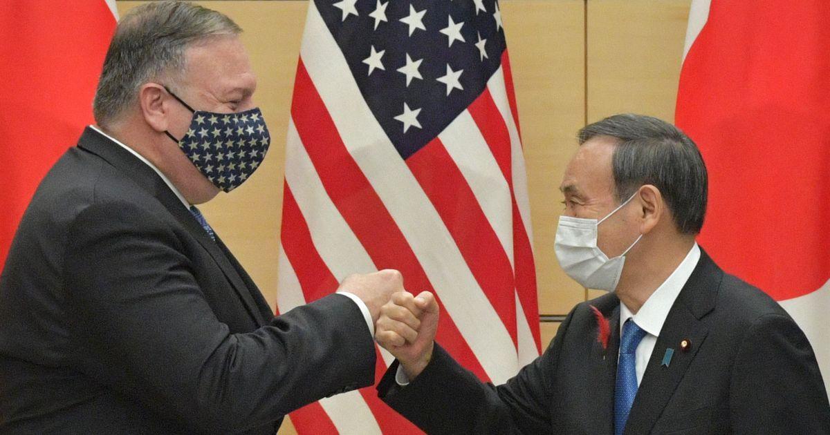 写真・図版 : 来日したポンペオ米国務長官(左)とグータッチをする菅首相=10月6日、首相官邸。朝日新聞社